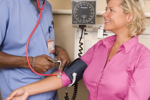 male-nurse-taking-woman-blood-pressure-patient