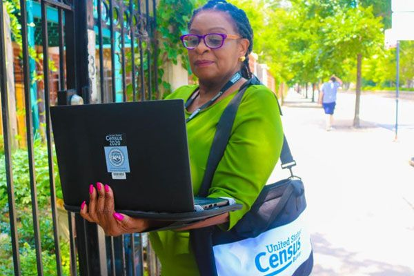Photo: Woman holding an open computer by a gate. The computer has a Census 2020 sticker on it