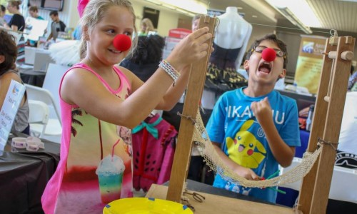 Two kids at the EdExploreSRQ ED-stravaganza with red clown noses