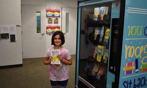 Photo: A third-grader at Garden Elementary shows off the book she picked from Sarasota County's first book vending machine