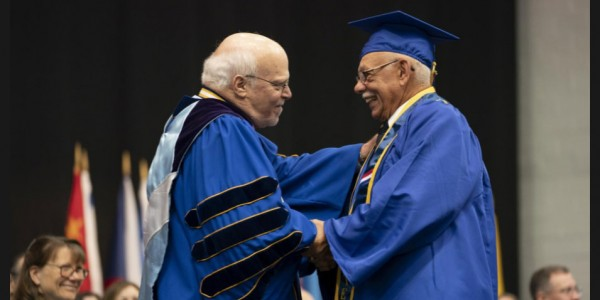 Photo: Anthony Rondello, right, receives his degree from Hofstra University on Long Island, New York