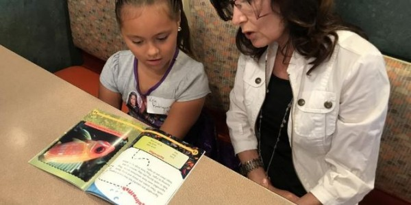 Raine Phillips, a volunteer mentor with the Anna Maria Oyster Bar's Dive Into Reading program, reads a book about fish with Kyla Rodriguez in July. [Herald-Tribune archive / Ryan McKinnon]