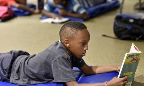 Gocio Elementary fifth-grader Jayven White, 10, reads during the Suncoast Campaign for Grade-Level Reading's Summer Book Challenge at the Robert L. Taylor Community Complex in Sarasota. [Herald-Tribune staff photo / Thomas Bender]