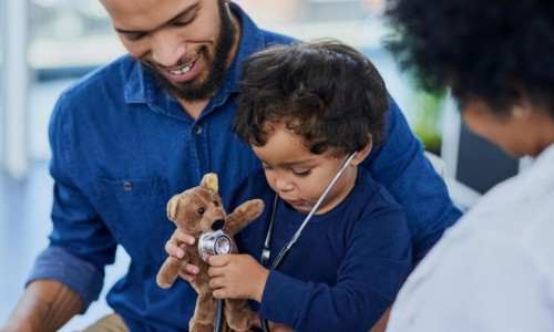 Photo: Father smiling at his child who is holding a teddy bear and checking its heartbeat with a stethoscope