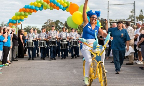 "Photo: Age-friendly character ""Girl"" riding a bike in front of the marching band"