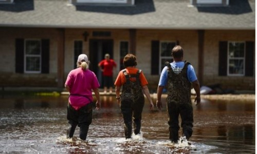 Local Texans walk through a flooded Orange, Texas neighborhood, Sept. 3, 2017. Hurricane Harvey formed in the Gulf of Mexico and made landfall in southeastern Texas, bringing record flooding and destruction to the region. (U.S. Air Force photo by Master S