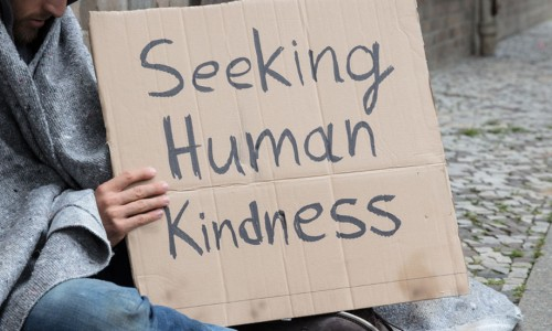 Homeless man holding sign that says seeking human kindness