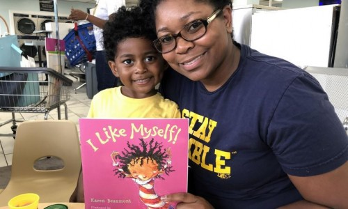 Photo: African American mother and daughter at the laundromat with a book entitled I like myself