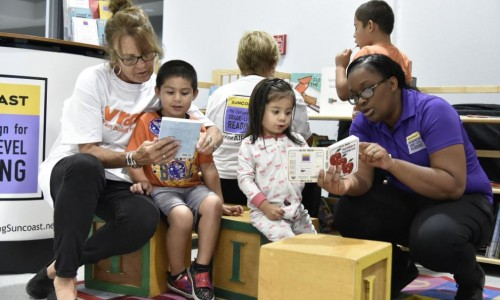 Photo: SCGLR Engagement Team members reading with kids at an event