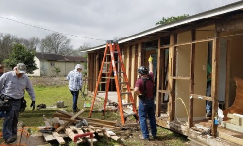 Photo: Three men rebuilding a house