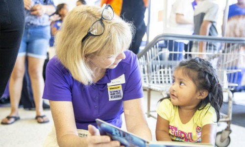 Photo: Beth Duda, director of SCGLR, reading to a little girl at the Pop Up Laundry event