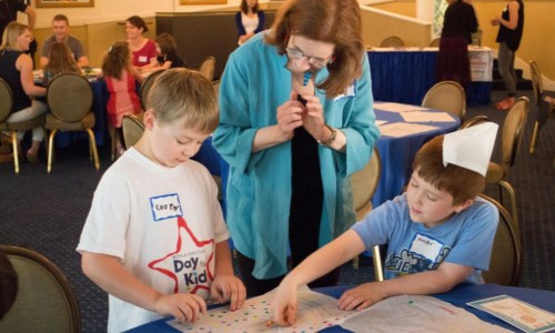 "Photo: Dr. Annie K. Fishel, author of ""Home for Dinner: Mixing Food, Fun, and Conversation for Happier Families and Healthier Kids"" talks to kids at a community event."