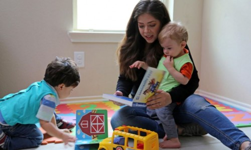 Adult female reading to and playing with two kids