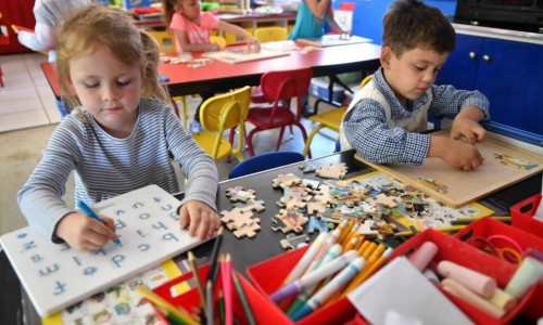 Preschool students work on writing and a puzzle