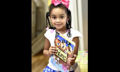 Little girl holding a book, smiling