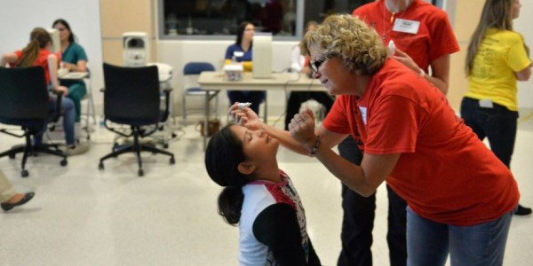 Volunteer at Remote Area Medical Clinic administering eye drops to a nine-year-old child