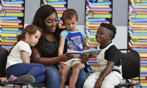 "Photo: Brittley Mayes, a recreation specialist at the Robert L. Taylor Community Complex, reads ""The Cat in the Hat"" to children during the Suncoast Campaign for Grade-Level Reading's Summer Reading Challenge."