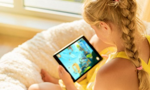 Photo: child holding a tablet and watching a program