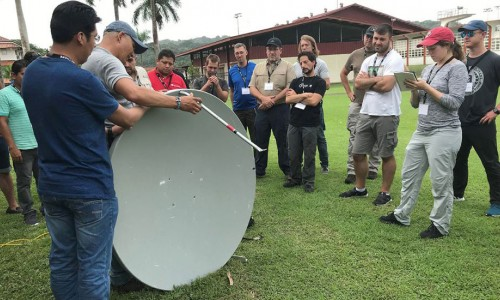 Photo: A diverse group of adult students are sanding in a semi-circle around a trainer who is demonstrating the proper way to assemble a satellite dish for internet connectivity.