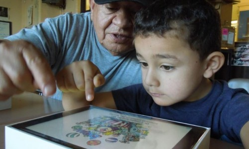 Photo: older adult teaching little boy to use technology