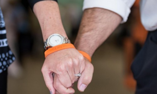 Photo: Older couple holding hands wearing Parkinson's Expo bracelets
