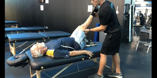 Photo: physical trainer at Gym SRQ works with a client on stretching