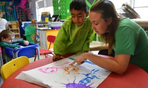Photo: Preschool student explains his painting to his teacher